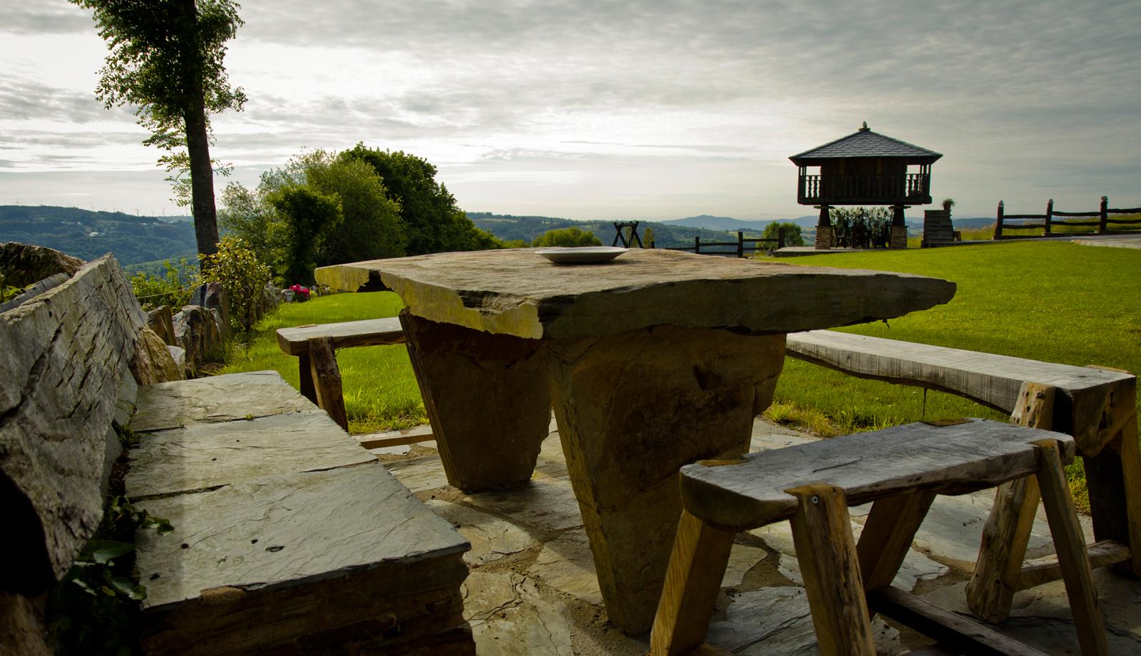 Mesa exterior con el horreo al fondo